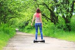 Kvinnan som utomhus rider en elektrisk sparkcykel - sväva brädet, det smarta jämviktshjulet, gyroskopsparkcykeln, hyroscooter, pe Royaltyfri Bild