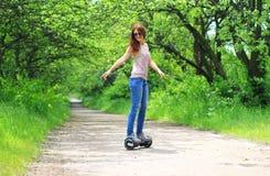 Kvinnan som utomhus rider en elektrisk sparkcykel - sväva brädet, det smarta jämviktshjulet, gyroskopsparkcykeln, hyroscooter, pe Arkivfoto