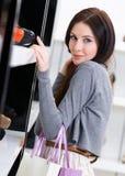 Kvinnan som väljer ett par av skodon shoppar in Arkivbild