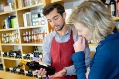 Kvinnan som väljer flaskvin shoppar in, med alkoholdrycker Arkivfoton