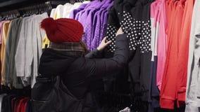 Kvinnan som väljer modekläder i detaljhandel, shoppar i stadsgallerian ben för bakgrundspåsebegrepp som shoppar den vita kvinnan lager videofilmer