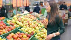 Kvinnan som väljer nya röda äpplen i livsmedelsbutik, producerar avdelning lager videofilmer