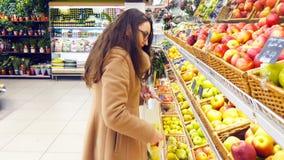 Kvinnan som väljer nya röda äpplen i livsmedelsbutik, producerar avdelning och att sätta den i plastpåse Den unga nätta flickan ä arkivfoton