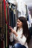 Kvinnan som väljer remmen på, shoppar Royaltyfria Bilder