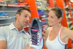 Kvinnan som väljer rinnande skor i sportar, shoppar Arkivbild