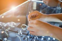 Kvinnan som väljer vigselringar på smyckendiamanten, shoppar arkivbild