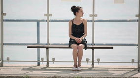 Kvinnan som väntar på en buss på hållplatsen, ser omkring och missa lager videofilmer
