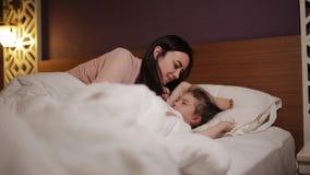 Kvinnan som vaknar unga flickan i säng som ler, fostrar att komma till det sova barnet stock video