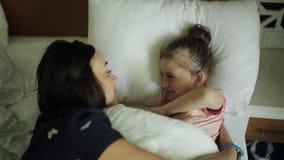 Kvinnan som vaknar unga flickan i säng som ler, fostrar att komma till det sova barnet arkivfilmer