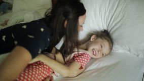 Kvinnan som vaknar unga flickan i s?ng som ler, fostrar att komma till det sova barnet arkivfilmer