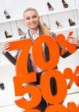 Kvinnan som visar procentsatsen av försäljningar på höjdpunkt, heeled skor fotografering för bildbyråer