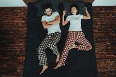 Kvinnan sover och snarkar på säng med mannen arkivbilder