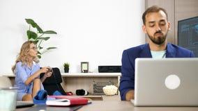 Kvinnan spelar en videospel på konsolen, medan hennes pojkvän arbetar på datoren i den samma vardagsrummet stock video
