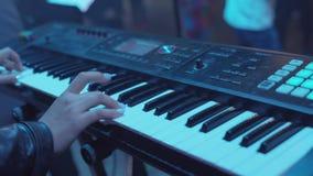 Kvinnan spelar vid händer på det vita digitala pianot, närbildskytte med defocus materiel Flickan spelar vid fingrar på lager videofilmer