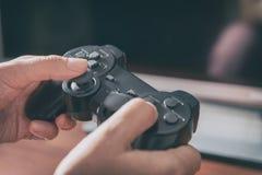 Kvinnan spelar videospelet genom att använda gamepaden arkivfoton
