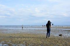 Kvinnan spenderar sommarsemestertid på vitt lågvatten för den sandiga stranden som tar selfie royaltyfria foton