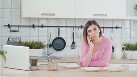 Kvinnan spenderar tid i kök, förbereder matställen som talar på telefonen arkivfilmer