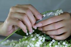 Kvinnan spikar, manikyr med blommor Nails täckte med nakenstudie spikar polermedel arkivfoton