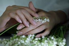 Kvinnan spikar, manikyr med blommor Nails täckte med nakenstudie spikar polermedel royaltyfri bild