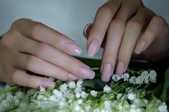 Kvinnan spikar, manikyr med blommor Nails täckte med nakenstudie spikar polermedel arkivbilder