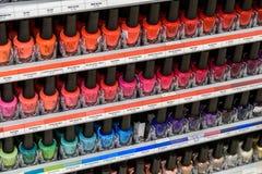 Kvinnan spikar polermedelprodukter som är till salu i skönhetsmedel, shoppar Royaltyfri Bild