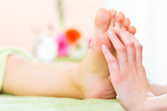 Kvinnan spikar in salongen som mottar fotmassage Royaltyfri Foto