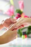 Kvinnan spikar in salongen som mottar handmassage Arkivbild