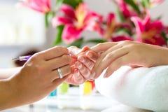 Kvinnan spikar in salonghälerimanicuren royaltyfria bilder