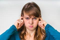 Kvinnan stänger öron med fingrar för att skydda från högt oväsen arkivfoton