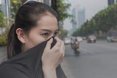 Kvinnan stänger hennes näsa med handen på grund av dålig trafikförorening arkivfoto