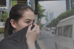 Kvinnan stänger hennes näsa med handen på grund av dålig trafikförorening royaltyfri bild