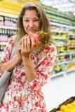 Kvinnan står i en supermarket med Pitaya (drakefrukt) i hans händer royaltyfria bilder