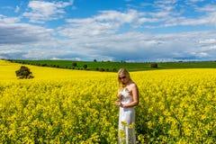 Kvinnan står i fält av canola lantliga Australien fotografering för bildbyråer