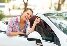 Kvinnan står nära den konvertibla bilen med tangenterna i hand Arkivfoto