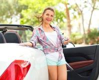 Kvinnan står nära den konvertibla bilen med tangenterna i hand Royaltyfri Bild