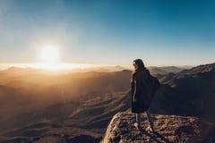 Kvinnan står på kanten av klippan på Mount Sinai mot bakgrund av soluppgång arkivbild
