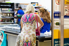 Kvinnan står på kassaapparaten och betalar för godset royaltyfri bild