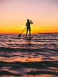 Kvinnan står upp skovellogi på skymning på ett plant varmt tyst hav med härliga solnedgångfärger Fotografering för Bildbyråer