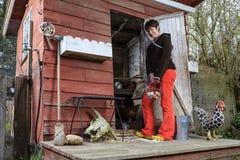 Kvinnan står utvändiga hållande ägg för den fega coopen i en korg Fotografering för Bildbyråer