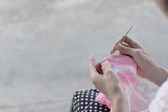 Kvinnan sticker en krok från ett rosa och vitt garn Arkivfoto