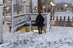 Kvinnan stiger ned till den underjordiska gångtunnelstationen under snöstorm I Royaltyfri Fotografi