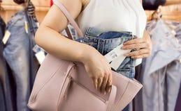 Kvinnan stjäler byxa på boutique arkivfoto