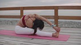 Kvinnan sträcker ben som utomhus gör fysisk övning och att sitta på golv lager videofilmer