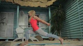 Kvinnan sträcker hennes armar, ben och baksida i sand nära huset lager videofilmer