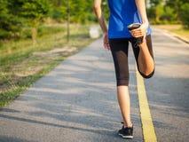 Kvinnan sträcker, innan han joggar Kondition- och livsstilconcep royaltyfri fotografi