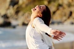 Kvinnan sträcker ut henne armar i glädje vid hav royaltyfria bilder