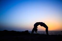Kvinnan sträcker yogasolnedgångkonturn Arkivfoto