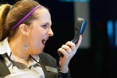Kvinnan svär med klienten vid telefonen royaltyfri foto