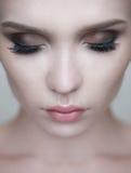 Kvinnan synar med härlig makeup och långa ögonfrans Royaltyfri Fotografi