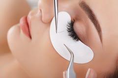 Kvinnan synar med långa ögonfranser Ögonfransförlängning